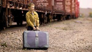 Poika seisoo matkalaukku kädessä vanhannäköisen junan edessä.