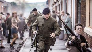 Sotilaita juoksee kaupunkimaastossa, myös tavallisia ihmisiä näkyy taustalla.