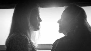 Närbild på Anna (Nina Gunke) och Esther (Anki Lidén) som står vid ett tågfönster och ser på varandra. Ur kortfilmen Guds tystnad.