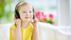 En liten flicka med hörlurar lyssnar på någonting