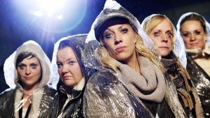 Kätevän emännän näyttelijät vesisateessa sadetakit päällä ja meikit valuneina.