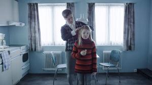 En kvinna fixar en liten flickas hår.