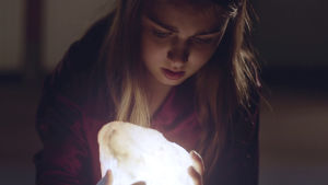 Flicka med en lysande sten i sina händer.