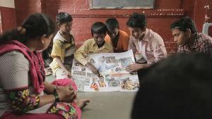 Intialaisia poikia kerääntyneenä yhteen isolle paperille tehdyn jonkinalisen esitelmän äärelle.