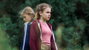Kaksi nuorehkoa tyttöä seisoo luonnossa selät toisiaan vasten.