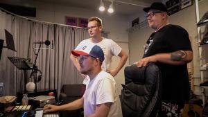 Kolme miestä musiikkistudiossa. Yksi istuu äänipöydän edessä, kaksi seisoo hänen takanaan.
