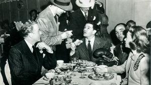 Ihmisiä syömässä ravintolassa. Päädyssä istuvan miehen puoleen on kumanrtuneena kaksi muuta miestä.