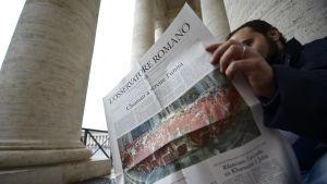 En man läser en upplaga av tidningen L'Osservatore Romano. Bilden är tagen 2013.