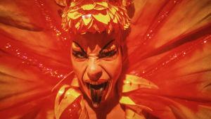Guy Pearcen näyttelemä drag queen lähikuvassa, täydessä loistossaan. Kuva elokuvasta Priscilla, aavikon kuningatar.