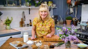 Nainen seisoo keittiössä pöydän ja leikkuulaudan takana, katsoo kameraan ja hymyilee.