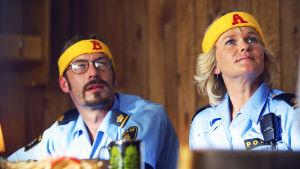 En manlig och en kvinnlig polis med gula pannband i filmen Kopps sitter vid ett bord.