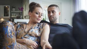 Mun ainoot 30 minsaa -sarjan Eveliina ja Ville eli Rebecca Viitala ja Ilkka Villi istuvat sohvalla sylikkäin, Eveliinan käsi Villen reidellä.