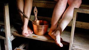 Kaksi naista istuu saunan lauteilla, kuvassa näkyy vain paljaat sääret. Etualalla saunakiulu.