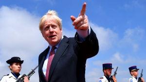 Boris Johnson anländer till Biarritz och pekar med fingret.