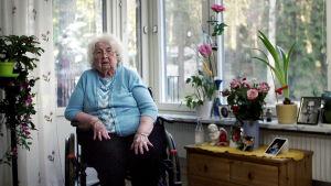 Gammal dam i vitt hår och blå tröja sitter i en rullstol