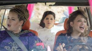 Kolme naista autossa, takapenkillä oleva hääpuvussa.