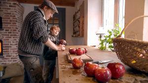 Mies ja poika keittiössä pilkkomassa omenia.