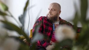 Laulaja Kasmir istuu sohvalla, etualalla kukkia epäterävänä.