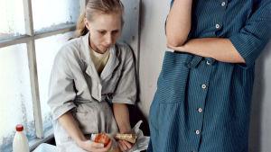 Iris (Kati Outinen) sitter på ett fönsterbräde med en smörgås i handen och ser uppgiven ut.