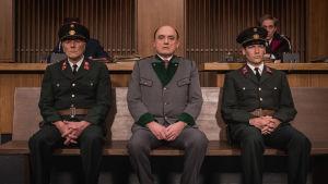 Sotarikoksista syytetty Franz Murer (Karl Fischer) istuu oikeudessa kahden poliisin välissä