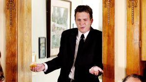 Nuori mies nojaa ovenkarmiin ja levittelee käsiään.
