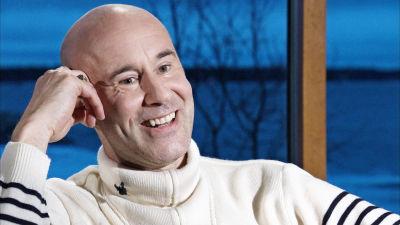 Mark Levengood ler och tittar åt sidan. Han lutar huvudet mot sin ena arm/hand.