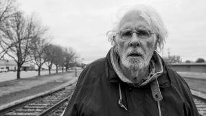 Bruce Dern puolilähikuvassa, seisoo raiteilla. Kuva elokuvasta Nebraska.
