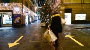 Kvinna med shoppingkassar går på mörk gata i Italien. Mitt på gatan står en julgran.