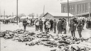 Sisällissodassa kuolleita makaa maassa, valkoisia seisoo ympärillä.