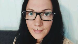Kvinna med mörkt hår och glasögon sitter lutad mot en vägg.