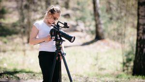Aurinkolasipäinen nuori nainen säätää jalustalla olevaa järjestelmäkameraa