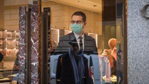 En försäljare i en modebutik i Milano bär andningsskydd.