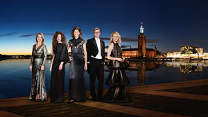 Neljä naista ja mies pukeutuneena iltapukuihin seisoo pimenevässä Tukholman illassa veden äärellä.