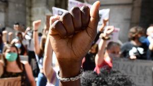 På bilden syns en knuten hand i förgrunden, i bakgrunden syns flera människor som håller upp en knuten näve och håller i plakat. Många är iklädda ansiktsskydd.