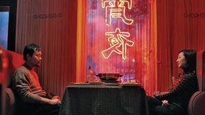 Mies ja nainen istuvat ravintolassa pöydän molemmin puolin ja katsovat toisiaan.