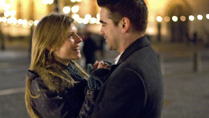 Nainen ja mies öisessä kaupunkikuvassa katsovat toisiaan, hymyilevät ja pitävät toisistaan kiinni