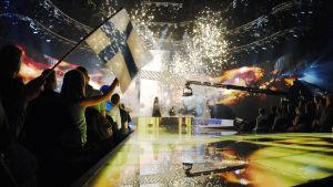 Hanna Pakarinen Euroviisuissa 2007, lavalla valoja ja kipinöitä ja Suomen lippuja, Hanna näkyy taustalla pienenä. Eurovision laulukilpailu, finaaliharjoitukset.