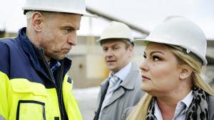 Ohjelmassa Pirunpelto Janne Sivula ja Piiku Tyrjälä katsovat tiukasti toisiaan, taustalla Relander.