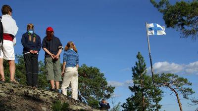 Nuoria partiolaisia seisoo korkealla kalliolla. Oikealla puolella Suomen lippu salossa.