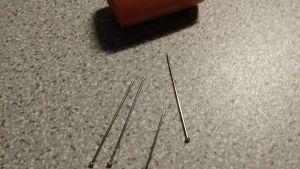 En bild på en korvbit ovh små spikar bredvid.