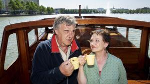 Kotikadun Mauri ja Monika kippistävät kahvikupeilla veneessä.