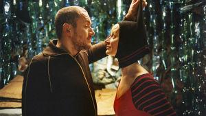 Nainen ja mies katsovat toisiaan. Mies vetää naista huppuhatun tupsusta.
