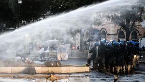 Kravallpolis använde bland annat vattenkanoner då de vräkte migranter som hade slagit läger på ett torg i Rom