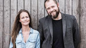 nainen ja mies nojaavat harmaaseen puuseinään, katsovat kameraan ja hymyilevät.