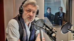 Mies istuu radiostudiossa mikrofonin edessä. Takana ikkunasta katsoo sisään kaksi miestä.