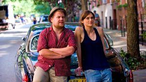 Mies ja nainen nojaavat auton perään ja katsovat oikealle viistoon.