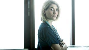 Nainen lääkärin vaatteissa katsoo kameraan.