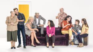 Alcantaran perhe sohvilla istumassa ja sen takana / ympärillä seisomassa.