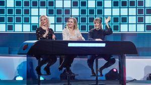 Krisse Salminen, Sanna Stellan ja Niina Lahtinen istuvat visailupöydän takana.