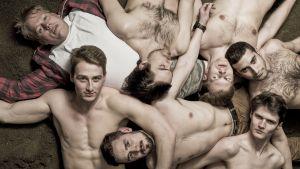 Miehiä makaa maassa läjässä ilman paitaa.